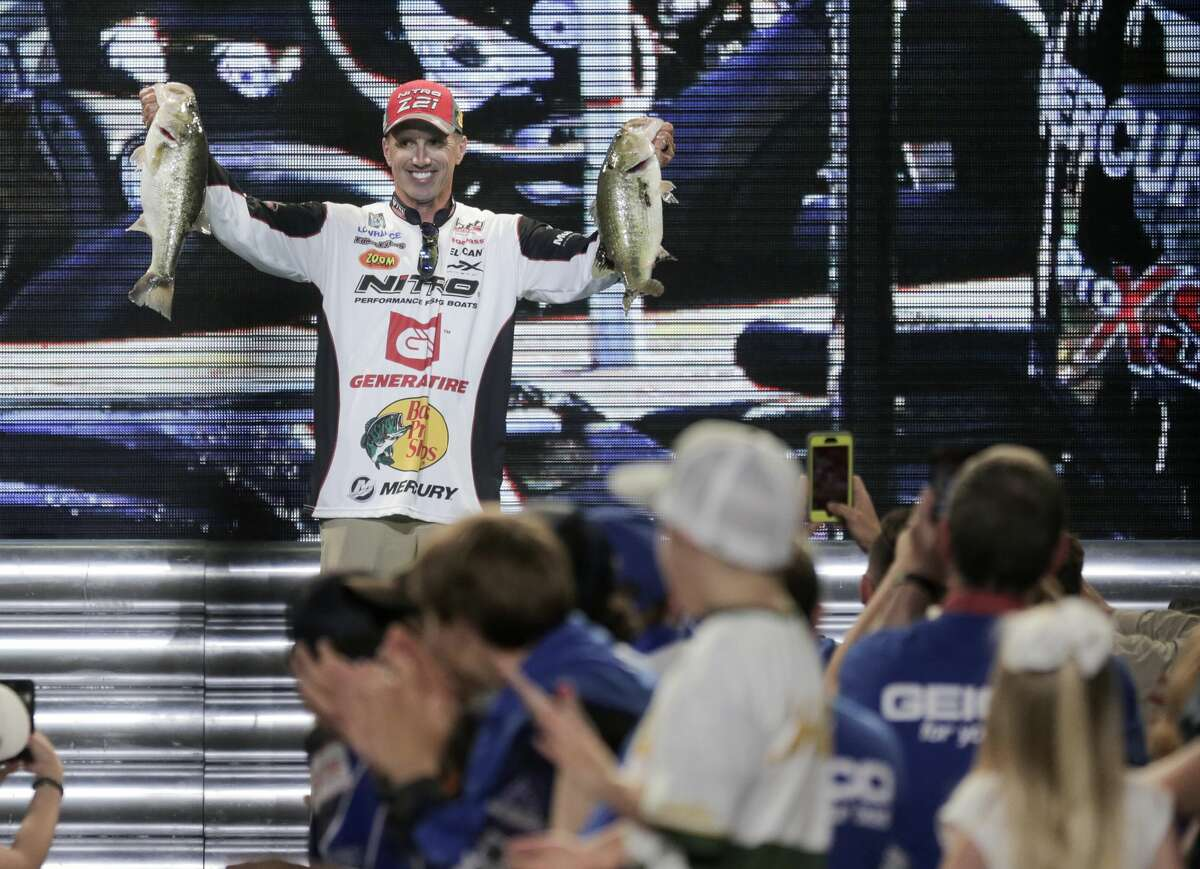 Edwin Evers holds up two bass he caught to place him in third after the day two weigh in for the Bassmaster Classicon Saturday, March 25, 2017, in Houston. ( Elizabeth Conley / Houston Chronicle )