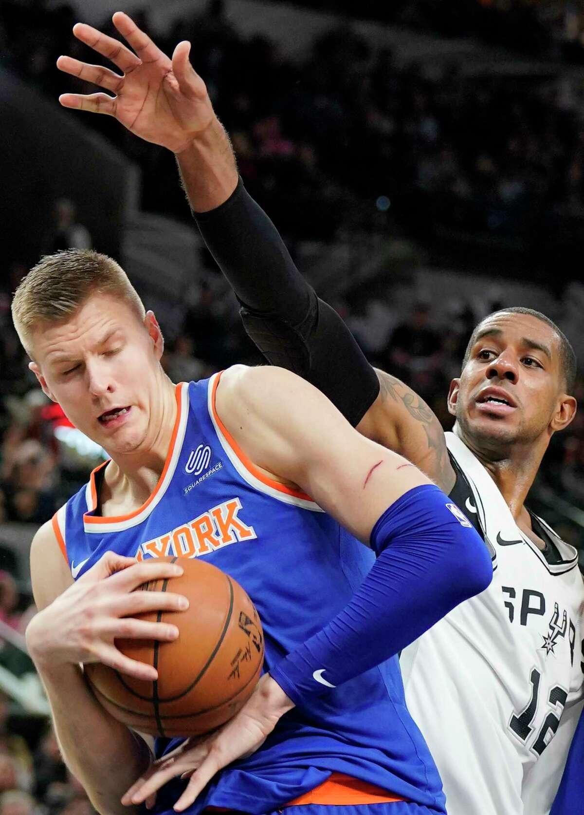 New York Knicks' Kristaps Porzingis, left, tangles with San Antonio Spurs' LaMarcus Aldridge during the second half of an NBA basketball game, Thursday, Dec. 28, 2017, in San Antonio. (AP Photo/Darren Abate)