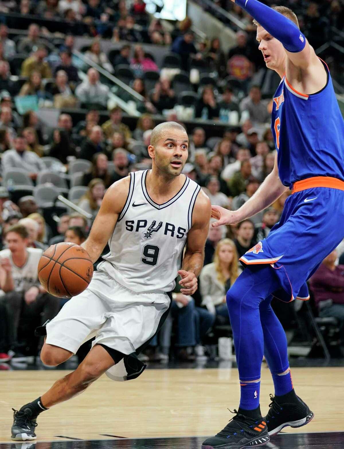 San Antonio Spurs guard Tony Parker (9) drives around New York Knicks' Kristaps Porzingis during the second half of an NBA basketball game, Thursday, Dec. 28, 2017, in San Antonio. (AP Photo/Darren Abate)