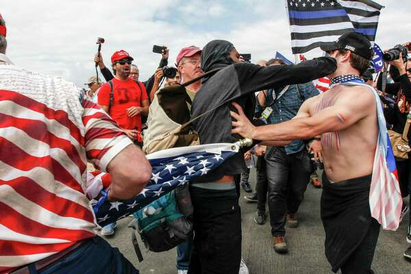 Supporters of President Donald Trump scuffle with counter-protesters during a rally on Saturday, March 25, 2017, in Huntington Beach, Calif. (Irfan Khan/Los Angeles Times via AP) ORG XMIT: CALOS301