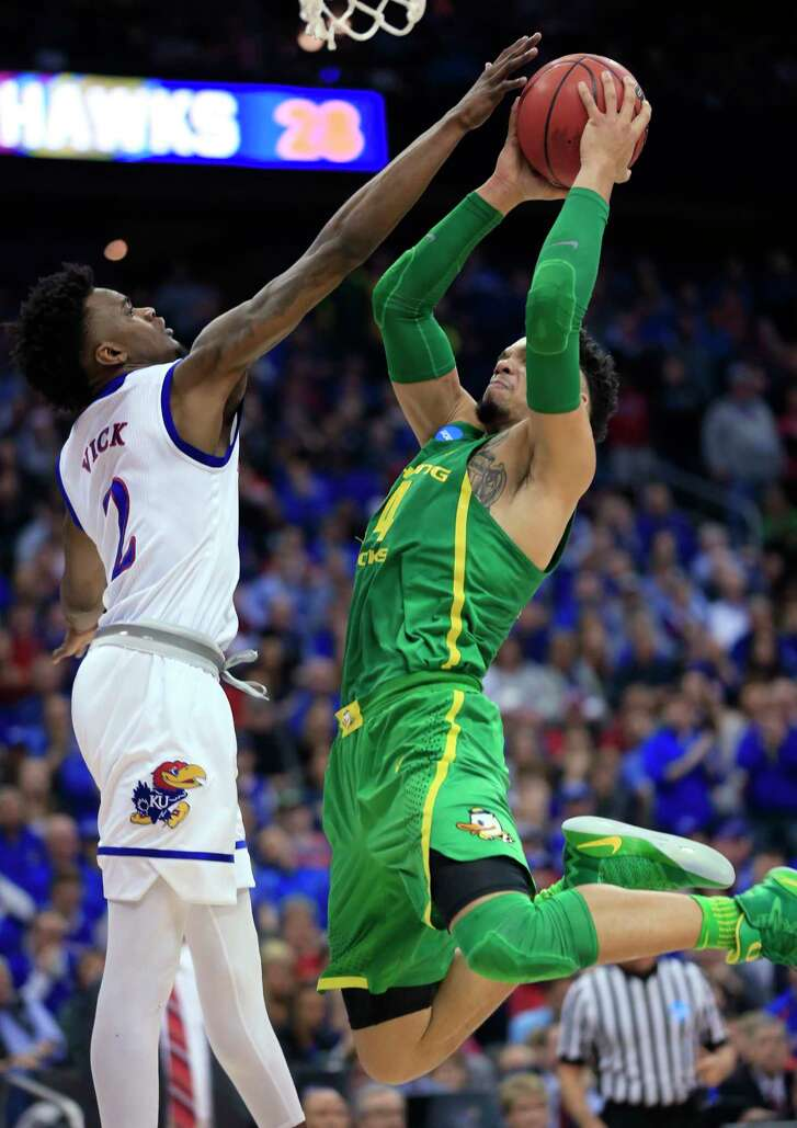 Oregon forward Dillon Brooks, right, shoots over Kansas guard Lagerald Vick during the first half of the Midwest Regional final of the NCAA men's college basketball tournament, Saturday, March 25, 2017, in Kansas City, Mo.