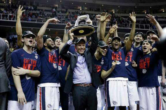 Gonzaga coach Mark Few joins his players in something they hadn't done before - hoisting an NCAA regional championship trophy.
