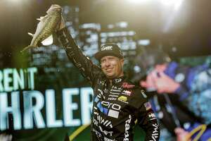 Brent Ehrler shows off one of the five largemouths he yanked from Lake Conroe on Saturday to lead the Bassmaster Classic.