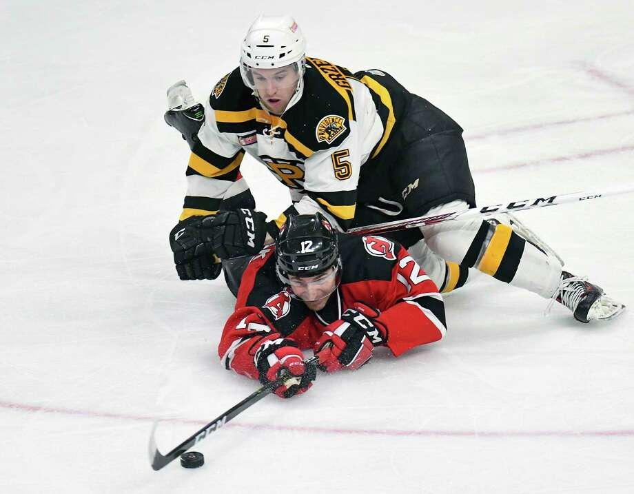 Albany Devils center Max Novak (12) and Providence Bruins defenseman Matt Grzelcyk (5) battle for the puck during the first period of an AHL hockey game in Albany, N.Y., Saturday, March 25, 2017. (Hans Pennink / Special to the Times Union) ORG XMIT: HP101 Photo: Hans Pennink / Hans Pennink