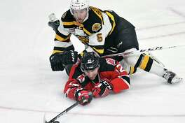 Albany Devils center Max Novak (12) and Providence Bruins defenseman Matt Grzelcyk (5) battle for the puck during the first period of an AHL hockey game in Albany, N.Y., Saturday, March 25, 2017. (Hans Pennink / Special to the Times Union) ORG XMIT: HP101