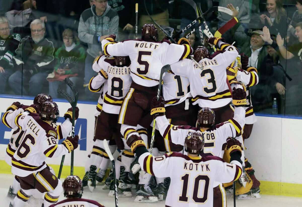 Minnesota-Duluth players surround Adam Johnson after his goal during overtime of the NCAA West Regional college hockey final against Boston University, Saturday, March 25, 2017, in Fargo, N.D. Minnesota-Duluth won 3-2. (AP Photo/Carlos Osorio) ORG XMIT: NDCO114