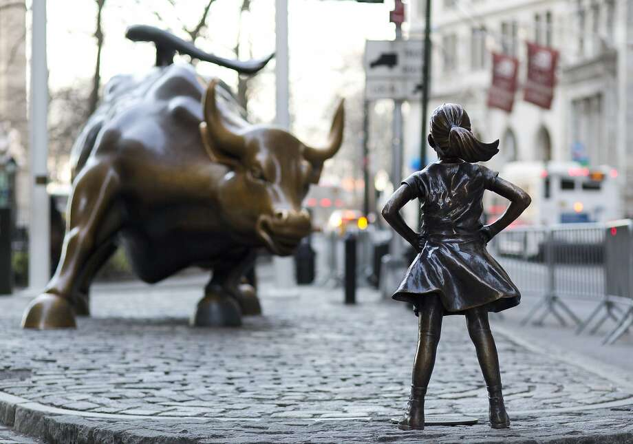 In this March 22, 2017 photo, the Charging Bull and Fearless Girl statues are sit on Lower Broadway in New York. Since 1989 the bronze bull has stood in New York City's financial district as an image of the might and hard-charging spirit of Wall Street. But the installation of the bold girl defiantly standing in the bull's path has transformed the meaning of one of New York's best-known public artworks. Pressure is mounting on the city to let the Fearless Girl stay. (AP Photo/Mark Lennihan) Photo: Mark Lennihan, Associated Press