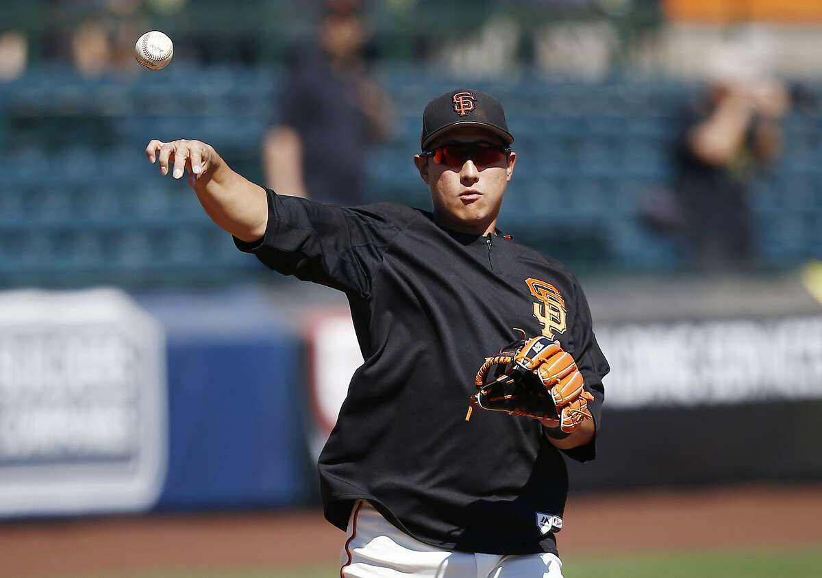 San Francisco Giants third baseman Jae-Gyun Hwang throws to first base during infield drills prior to a spring training baseball game against the Milwaukee Brewers Sunday, March 19, 2017, in Scottsdale, Ariz. (AP Photo/Ross D. Franklin)