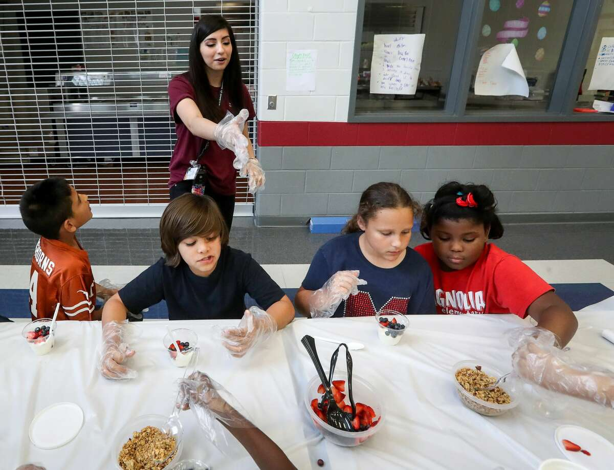 Samantha Torres, rear, a nursing student from Alvin Community College and activity coordinator, gives a lesson on nutrition to Isaac Pedraza, front from left, Joaquin Izaguirre, Josee Buchheight and Lori Taylor during an after-school program at Magnolia Elementary School, Friday, March 24, 2017, in Pearland. ( Jon Shapley / Houston Chronicle )