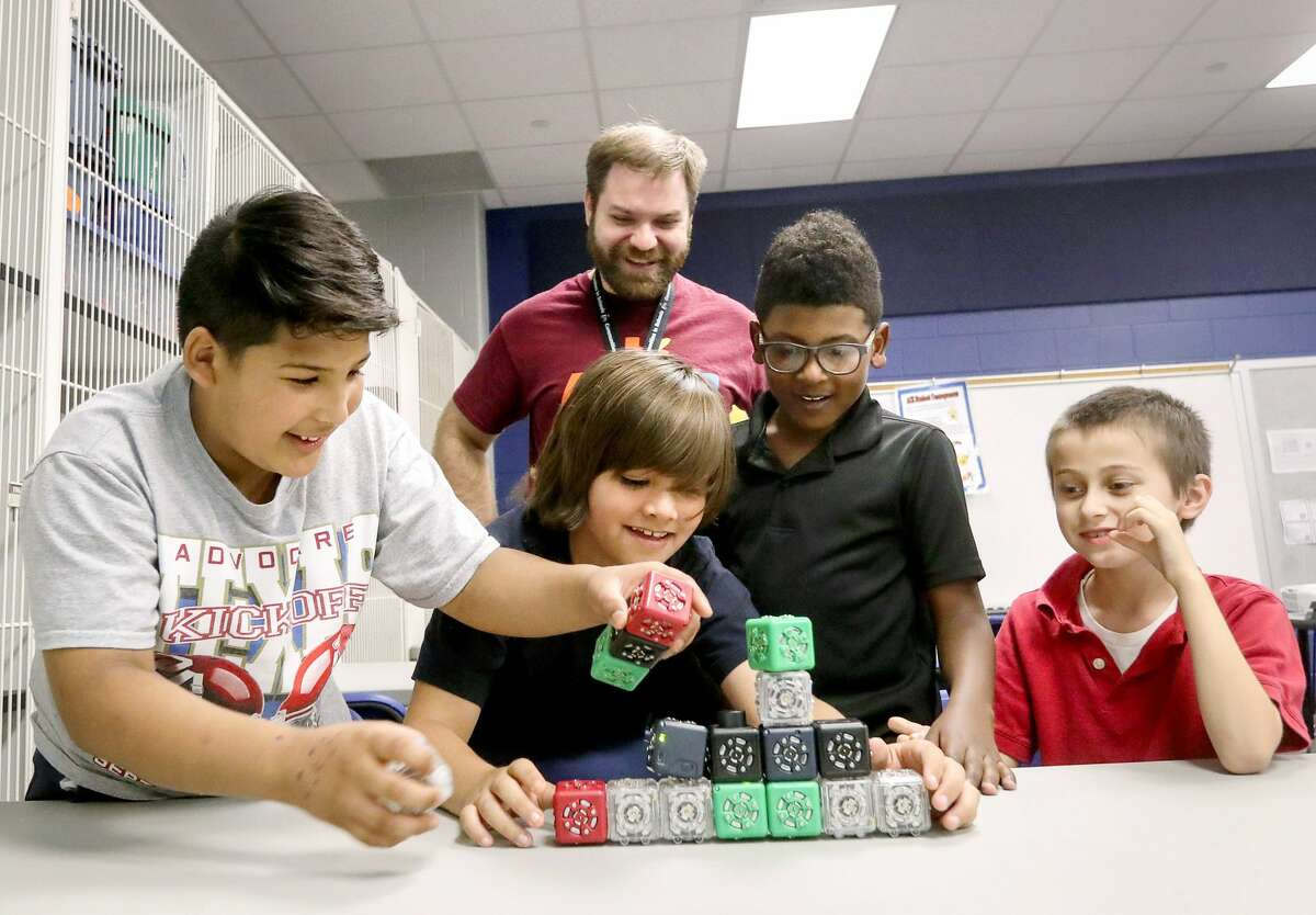 Travis Hayes, rear-center, an activity coordinator, looks on as Marc Pedraza, front from left, Joaquin Izaguirre, Roy Johnson and Aden Sitta play with robotic cubes during an after-school program at Magnolia Elementary School, Friday, March 24, 2017, in Pearland. When the cubes are combined with other ones, they move and perform tasks. Hayes uses the cubes to introduce the children to computer skills and coding. ( Jon Shapley / Houston Chronicle )