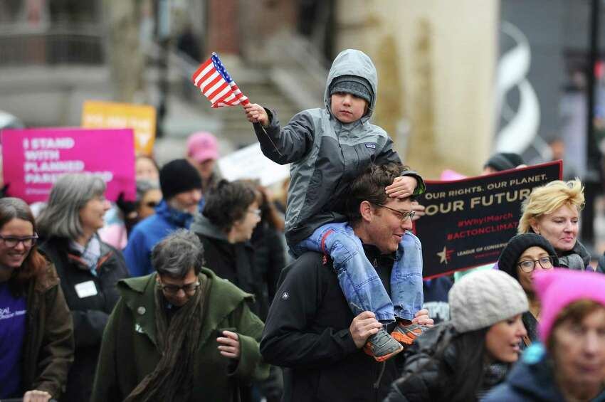 Seven-year old Andrew Meisel, of Westport, waves a flag while sitting on his father's shoulders during CT on the MOVE's