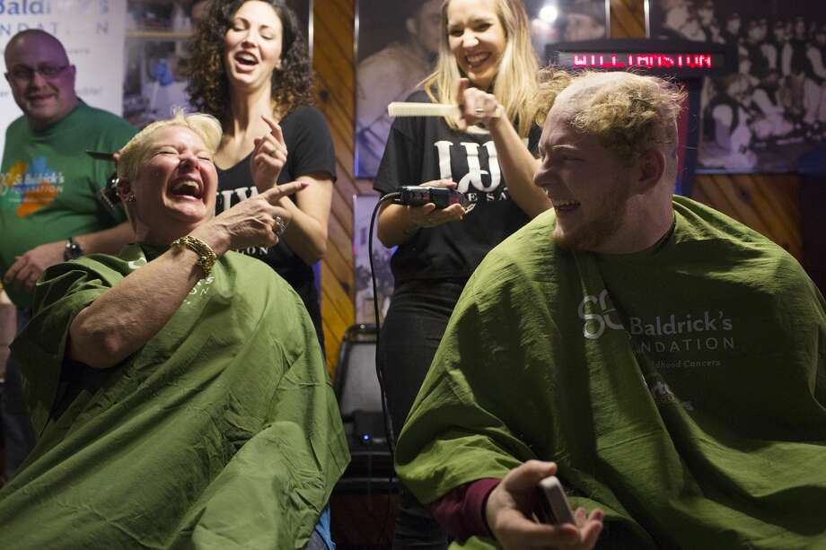 THEOPHIL SYSLO | For the Daily News Livonia resident Julie LaChance reacts to seeing her son's half shaved head Michael LaChance, 18, Central University of Michigan student, while participating in a head shaving fundraiser for cancer at The Boulevard Lounge on Sunday. Photo: Theophil Syslo