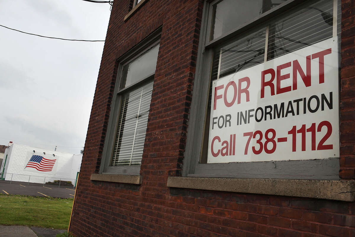 """UTICA, NY - MAY 14: A """"for rent"""" sign hangs in a window of an empty factory on May 14, 2012 in Utica, New York. Like many upstate New York communities, Utica is struggling to make the transition from a former manufacturing hub. The city's individual poverty rate is twice the national average with an unemployment rate of 9.8% as of February 2012. Citing Utica's weakening financial margins over the past two years, Fitch Ratings downgraded its credit rating on Utica by two notches to a triple-B, two rungs above junk territory. (Photo by Spencer Platt/Getty Images)"""