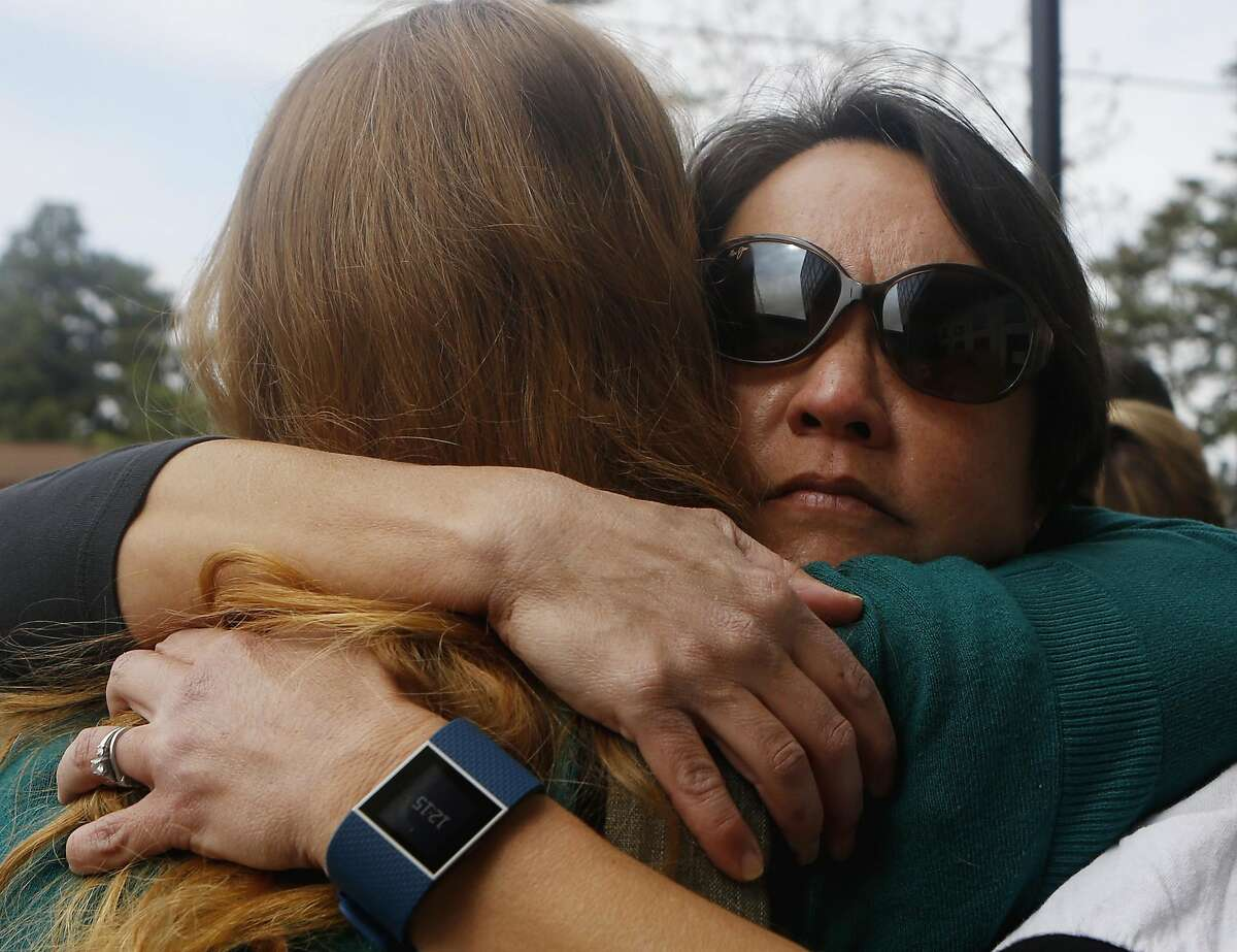 Alexandra Campbell, left, and Laurie Roberts, right, embrace after an emotional speech during a gathering in response the cyber bullying, at Albany High School on Sunday, March 26, 2017, in Albany, Calif.