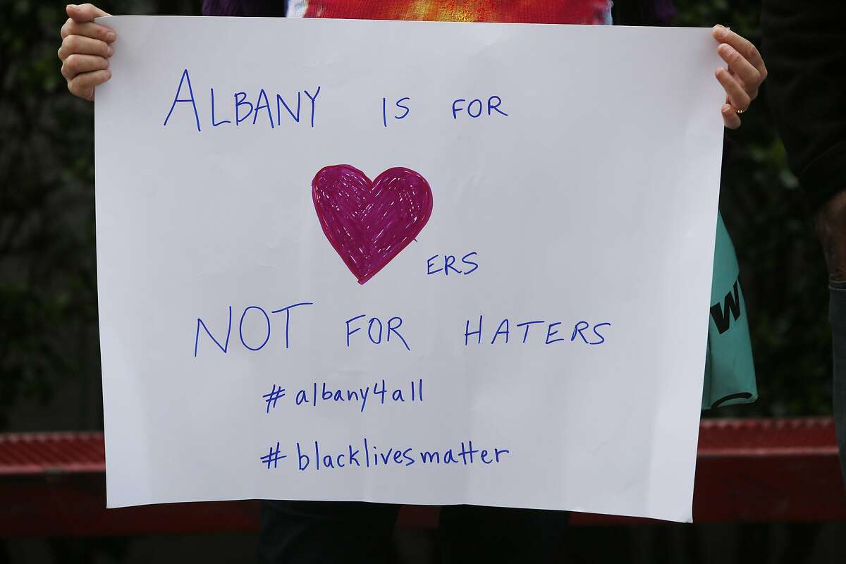 A woman holds up a sign in the crowd at a gathering in response the cyber bullying, at Albany High School on Sunday, March 26, 2017, in Albany, Calif.