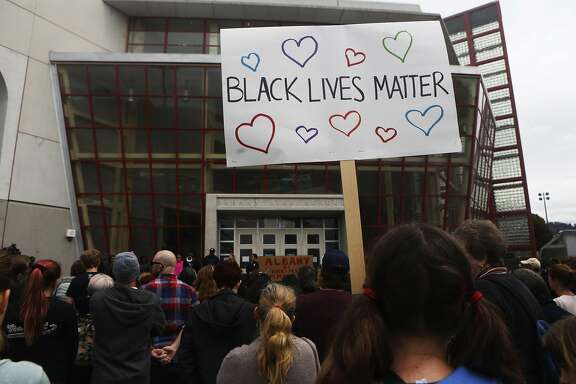 "A crowd member holds a sign reading ""Black Lives Matter""  at  a gathering in response the cyber bullying, at Albany High School on Sunday, March 26, 2017, in Albany, Calif.on Sunday, March 26, 2017, in Albany, Calif."