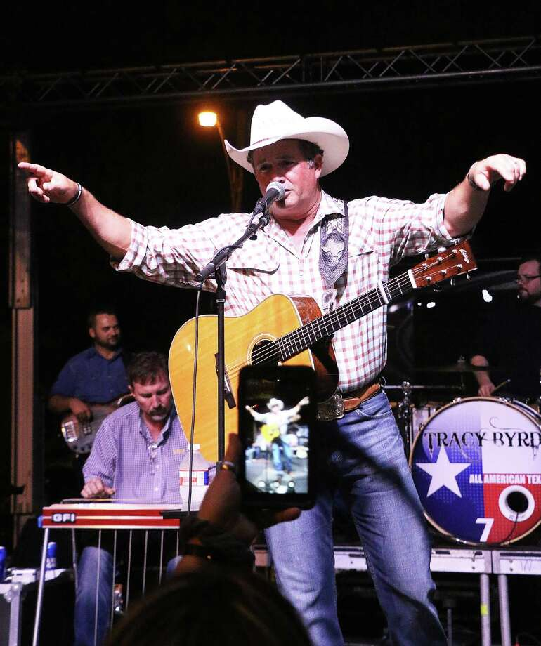 One fan holds up her cell phone to record country artist Tracy Byrd during his concert last Friday night at the Liberty Jubilee. Byrd sang for about an hour before the rain came again. Photo: David Taylor