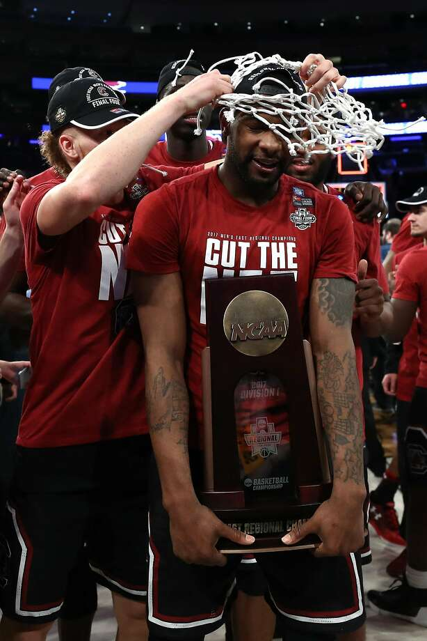 Sindarius Thornwell is fitted with a trophy and a net for South Carolina's regional title. Photo: Elsa, Getty Images