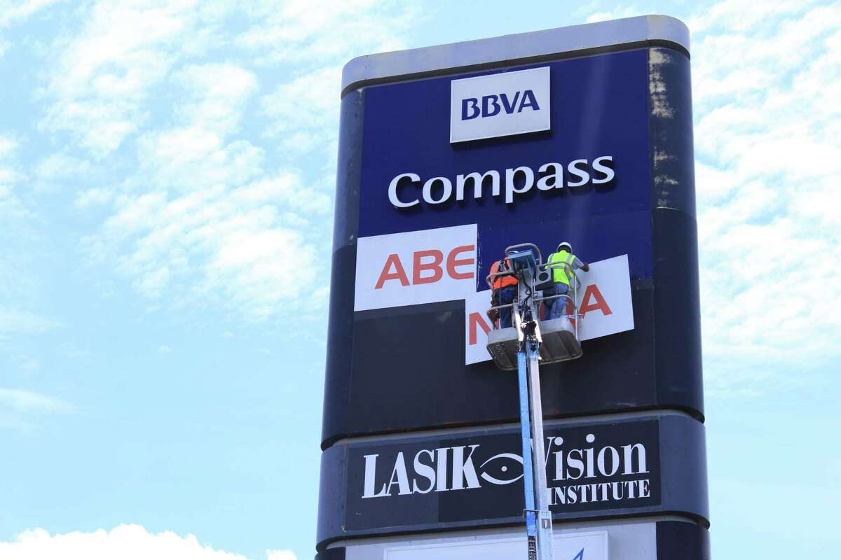 Workers at the Mercantile Building on Loop 410 take down a sign for Spanish firm Abengoa and replace it with one for Garney Construction. Garney took over controlling interest in a massive water pipeline, which will bring more water to San Antonio Water System, after Abengoa found itself facing serious financial problems.