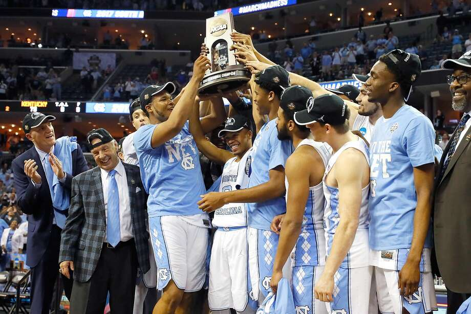 Head coach Roy Williams (left) stands back and lets his North Carolina players have some quality time with the South trophy. Photo: Kevin C. Cox, Getty Images
