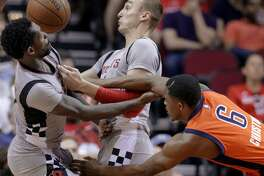 Houston Rockets' Patrick Beverley, left, and Sam Dekker compete for a rebound against Oklahoma City Thunder's Semaj Christon (6) during the second half of an NBA basketball game in Houston, Sunday, March 26, 2017. (AP Photo/Michael Wyke)
