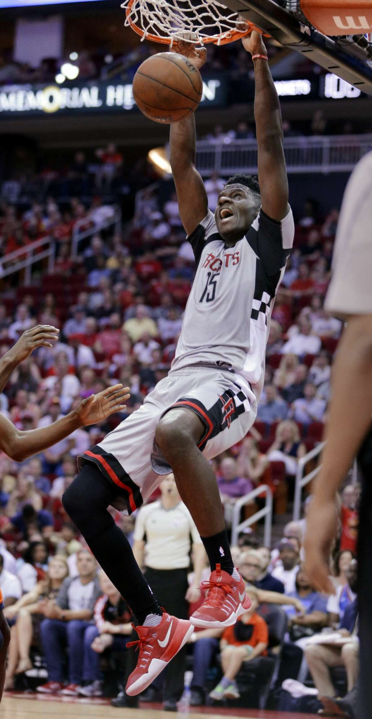 Houston Rockets' Clint Capela (15) hangs from the rim after a dunk against the Oklahoma City Thunder during the second half of an NBA basketball game in Houston, Sunday, March 26, 2017. Capela received a technical foul. (AP Photo/Michael Wyke)