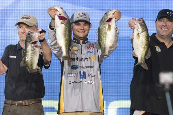 Jordan Lee, center, holds up his stringer of fish with Trip Weldon, left, and Dave Mercer, right, after taking the lead in the final round of the Bassmasters Classic during the final day weigh in at Minute Maid Park on Sunday, March 26, 2017, in Houston. ( Brett Coomer / Houston Chronicle )