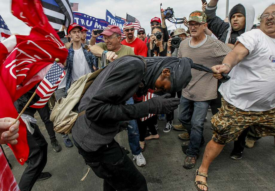 Pro-President Trump and anti-Trump protestors scuffle during a rally on Saturday, March 25, 2017, in Huntington Beach, Calif. (Irfan Khan/Los Angeles Times via AP) Photo: Irfan Khan, Associated Press