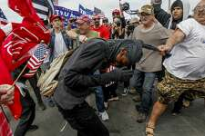 Pro-President Trump and anti-Trump protestors scuffle during a rally on Saturday, March 25, 2017, in Huntington Beach, Calif. (Irfan Khan/Los Angeles Times via AP)