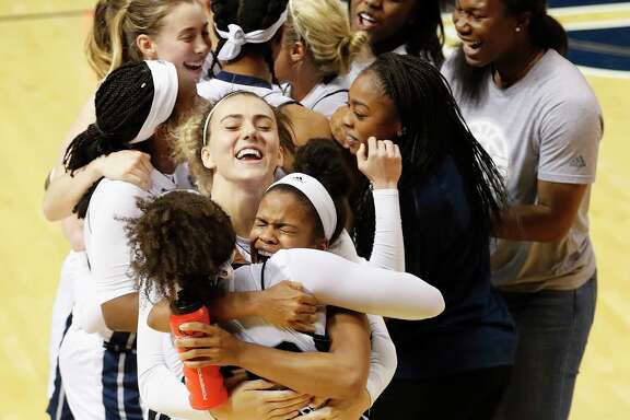 Tournament MVP Maya Hawkins, center, gets a hug from Rice's Jasmine Goodwine as the Owls celebrate winning the Women's Basketball Invitational title.
