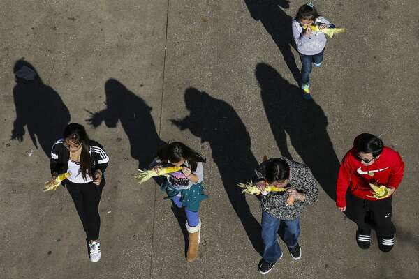 A family snacks on roasted corn at the Houston Livestock Show and Rodeo Monday, March 13, 2017 in Houston. ( Michael Ciaglo / Houston Chronicle )