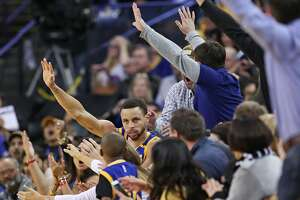 Golden State Warriors' Stephen Curry celebrates a basket after ending up in first row of seats in 4th quarter during Warriors' 106-94 win over Memphis Grizzlies in NBA game at Oracle Arena in Oakland, Calif., on Sunday, March 26, 2017.