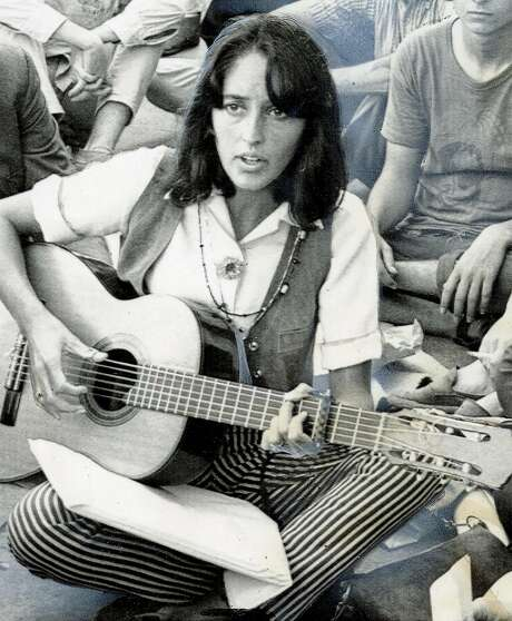 Folk singer Joan Baez sits on the sidewalk at the corner of Haight and Ashbury and serenades hippies and tourists in a spontaneous concert with a borrowed guitar. The concert was part of the wealthy singer's four-day visit to the place of origin of the hippies subculture of bare feet, sandals, beards, LSD and marijuana. Photo: Associated Press, 1967