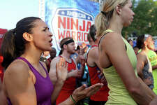 American Ninja Warrior San Antonio competitor Catherine Resigner, 36, (left) and others cheer as they look at the course.