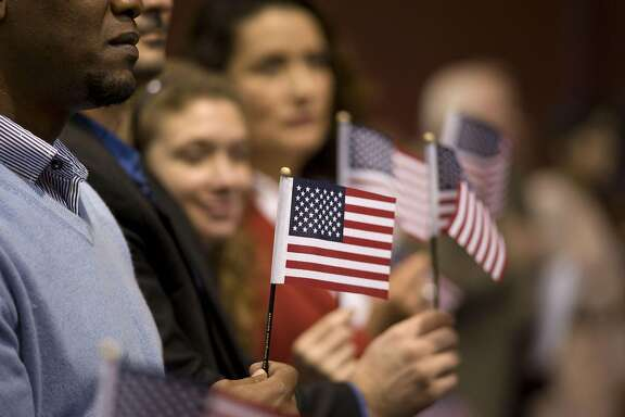"People hold miniature American flags during a naturalization ceremony in San Diego, California, U.S., on Wednesday, March 22, 2017. Hawaii's attorney general is seeking to extend a temporary restraining order blocking Donald Trump's revised travel ban, citing the president's own words as evidence that the new policy is merely a ""subterfuge."" Photographer: David Maung/Bloomberg"