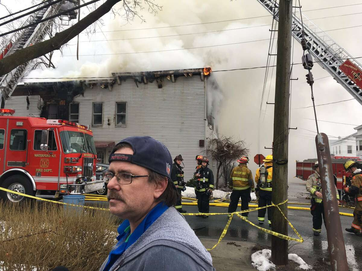 Resident Albert Manwarning took his two children to school Monday morning and returned home to find the place in flames. Firefighters spent hours trying to extinguish the fire. Manwaring said his cat missing and all equipment for maintenance business ruined. (Emily Masters / Times Union)