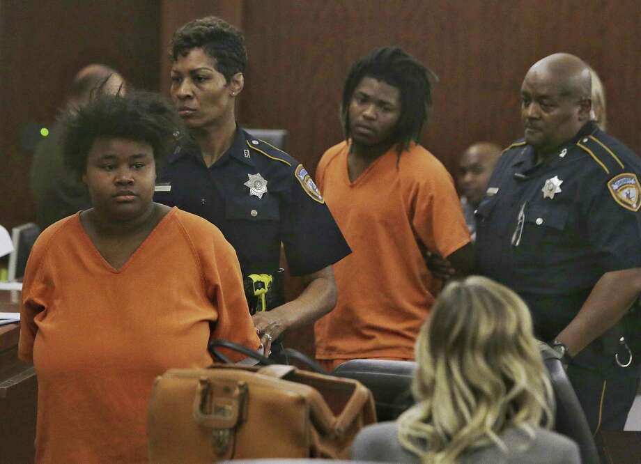 Courtney Burks, left, and her co-defendant,  Shaquan Bennett, are escorted from an appearance in the Harris County 179th Criminal Court Monday, March 27, 2017. The two 18-year-olds are accused of killing a 56-year-old man, whose body was found earlier this month in a burning dumpster in east Houston. They were charged Thursday with capital murder. Photo: Melissa Phillip / Houston Chronicle 2017