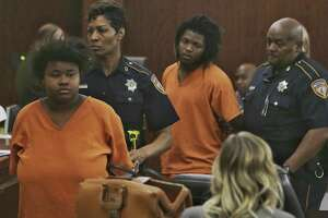 Courtney Burks, left, and her co-defendant,  Shaquan Bennett, are escorted from an appearance in the Harris County 179th Criminal Court Monday, March 27, 2017. The two 18-year-olds are accused of killing a 56-year-old man, whose body was found earlier this month in a burning dumpster in east Houston. They were charged Thursday with capital murder.
