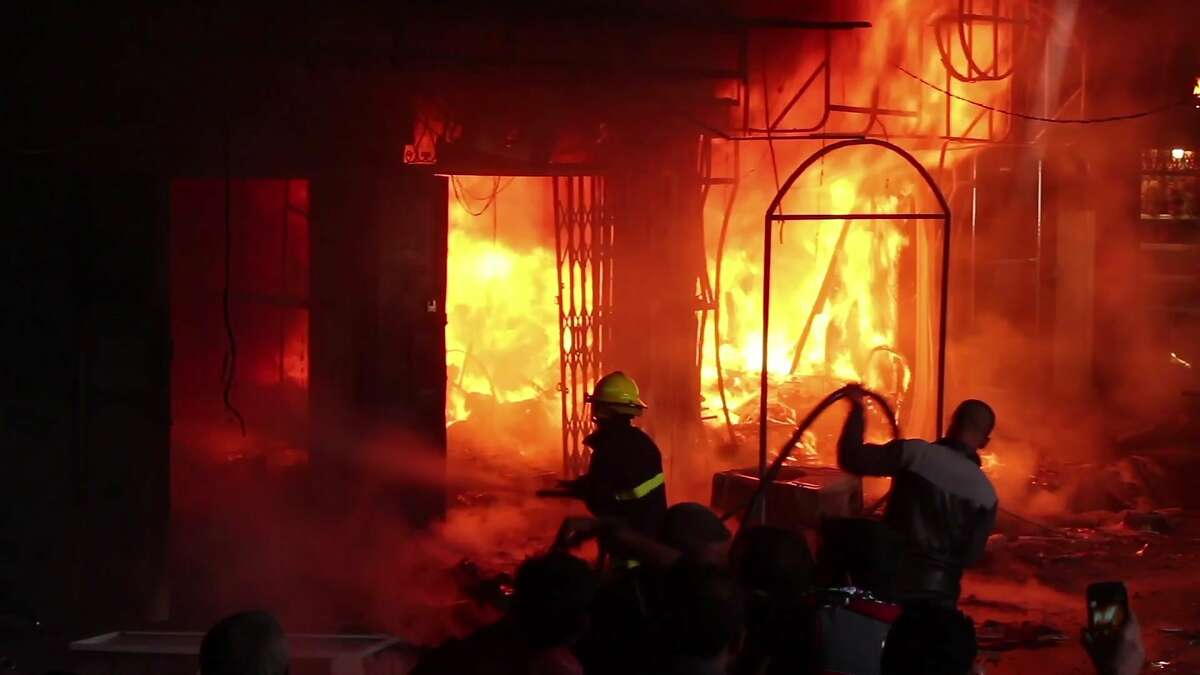 In this image taken from a video footage, a fireman tries to extinguish fire in multiple market stalls at Nabi Younus market in east Mosul, Iraq, Sunday, March 26, 2017. At least two people were killed and many others injured after three projectiles hit the busy Nabi Younus market in east Mosul on Sunday afternoon. (AP Photo)