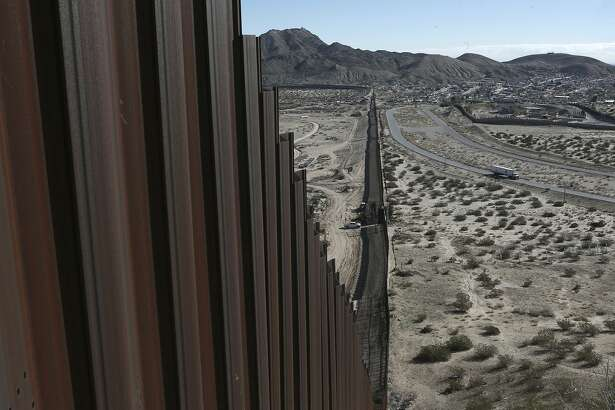FILE - This Jan. 25, 2017, file photo shows a truck driving near the Mexico-US border fence, on the Mexican side, separating the towns of Anapra, Mexico and Sunland Park, New Mexico. President Donald Trump will face many obstacles in building his �big, beautiful wall� on the U.S.-Mexico border, including how to pay for it and how to contend with unfavorable geography and the legal battles ahead.  (AP Photo/Christian Torres, File)
