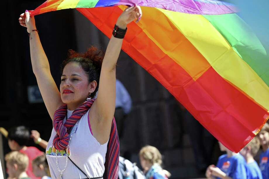 Erika Flores Casasola, of San Antonio, raises the gay pride flag during a rally in front of the state Capitol building, Monday, March 20, 2017. Members and supporters of the LGBTQ community rallied and voiced their opposition to SB6. Known as the bathroom bill, it regulates the usage of the facilities by making transgender people use the bathroom based on their birth gender. Photo: JERRY LARA / San Antonio Express-News / © 2017 San Antonio Express-News
