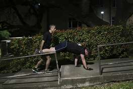 James Andrews, rights, climbs up stairs as he partners with Francisco Robelo for a wheelbarrow exercise.