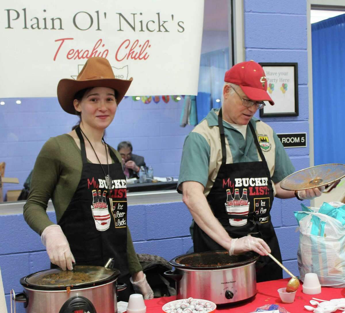 Nick Wolf, right, scoops some chili while co-worker Chloe Taub looks on during the Danbury Westerners' ninth-annual Chili Warm-Up at the Danbury Sports Dome March 26, 2017.