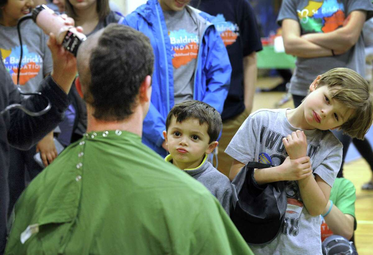 Brothers Marco, 4, and Dylan, 6, watch their father, Brookfield High School teacher Mike Smith get his head shaved for charity Monday evening, April 11, 2016. Students and teachers were among those who participated in a St. Baldrick's fundraiser at the high school to raise money for pediatric cancer patients.