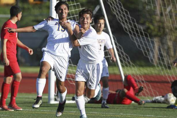 Brandan Garza (left) celebrates with Jonathan Rocha after his second goal as Alamo Heights plays Austin Travis at Orem Stadium in a Class 5A bidistrict playoff match on March 24, 2017.