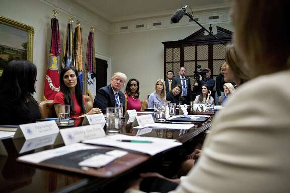 U.S. President Donald Trump and daughter Ivanka Trump (center) listen during a meeting with female small-business owners Monday in the Roosevelt Room of the White House.