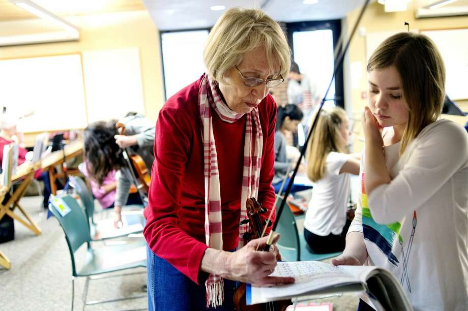 Violin instructor Janet Kroon, left, helps student Amilia Robinette before the Jolly Hammers and Strings Dulcimers concert on Saturday at the Chippewa Nature Center. The concert featured Kroon's students. Photo: NICK KING | Nking@mdn.net