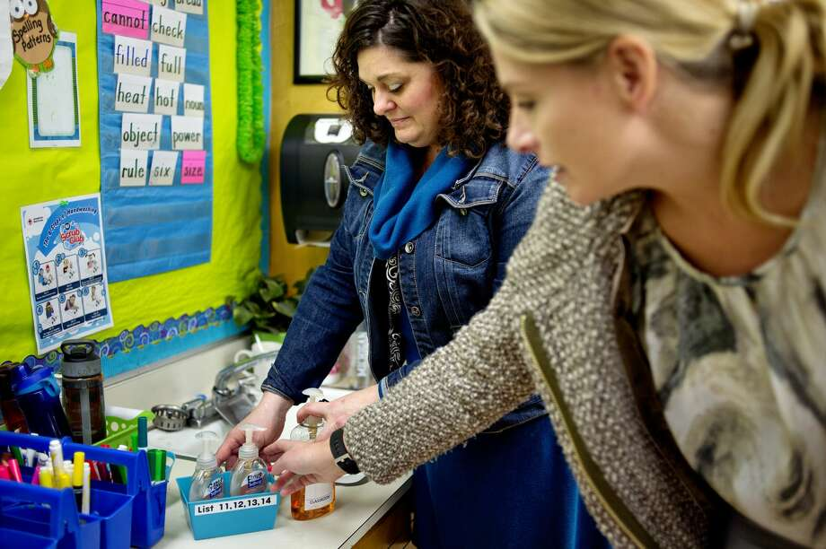 Second grade teacher Heather Shanteau, left, and parent Dagney Wysong, right, show off the classroom's Scrub Club soap kit on Monday at Siebert Elementary.  Wysong and other parents along with the school's staff got the hand washing program started. The whole school is competing to see who can be the cleanest. Siebert has turned washing hands into a competition with each class receiving containers of soap. The class that uses the most by spring break will receive a pizza party. The goal is to have the kids wash their hands more to try and prevent the spread of sickness. Photo: NICK KING | Nking@mdn.net