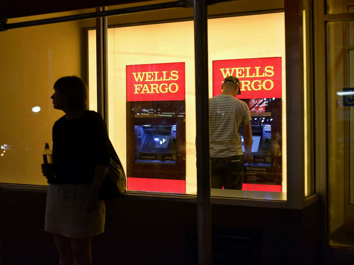 FILE - In this Sept. 21, 2016, file photo, a customer uses a Wells Fargo bank ATM in New York. On Tuesday, March 21, 2017, Wells Fargo announced plans to upgrade all 13,000 of its ATMs to allow customers to access their funds using their cellphones instead of traditional bank cards. (AP Photo/Patrick Sison, File)