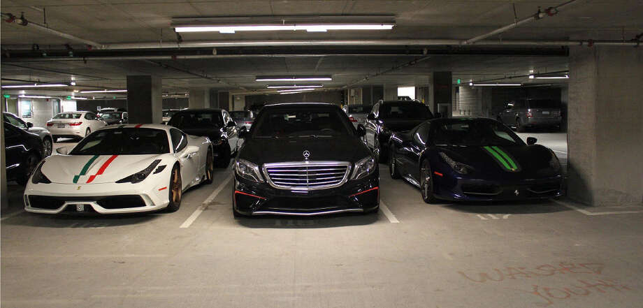 When Maziar Rezakhani was arrested in October 2015, federal agents found three of his cars parked in the garage of his luxury downtown Bellevue apartment. From left to right, a white Ferrari Speciale that Rezakhani obtained in June 2015, a Mercedes-Benz that he obtained in November 2014, and a blue Ferrari Spider that he obtained in December 2014. Rezakhani bought the cars while conducting a fraud that would help force the sale of a Seattle-area bank. Photo: U.S. Department Of Justice